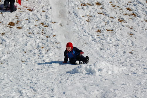 Toddler Child sledding on his bum.