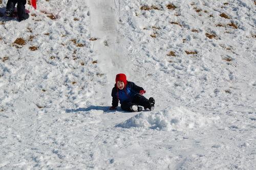 Toddler Child sledding on his bum.